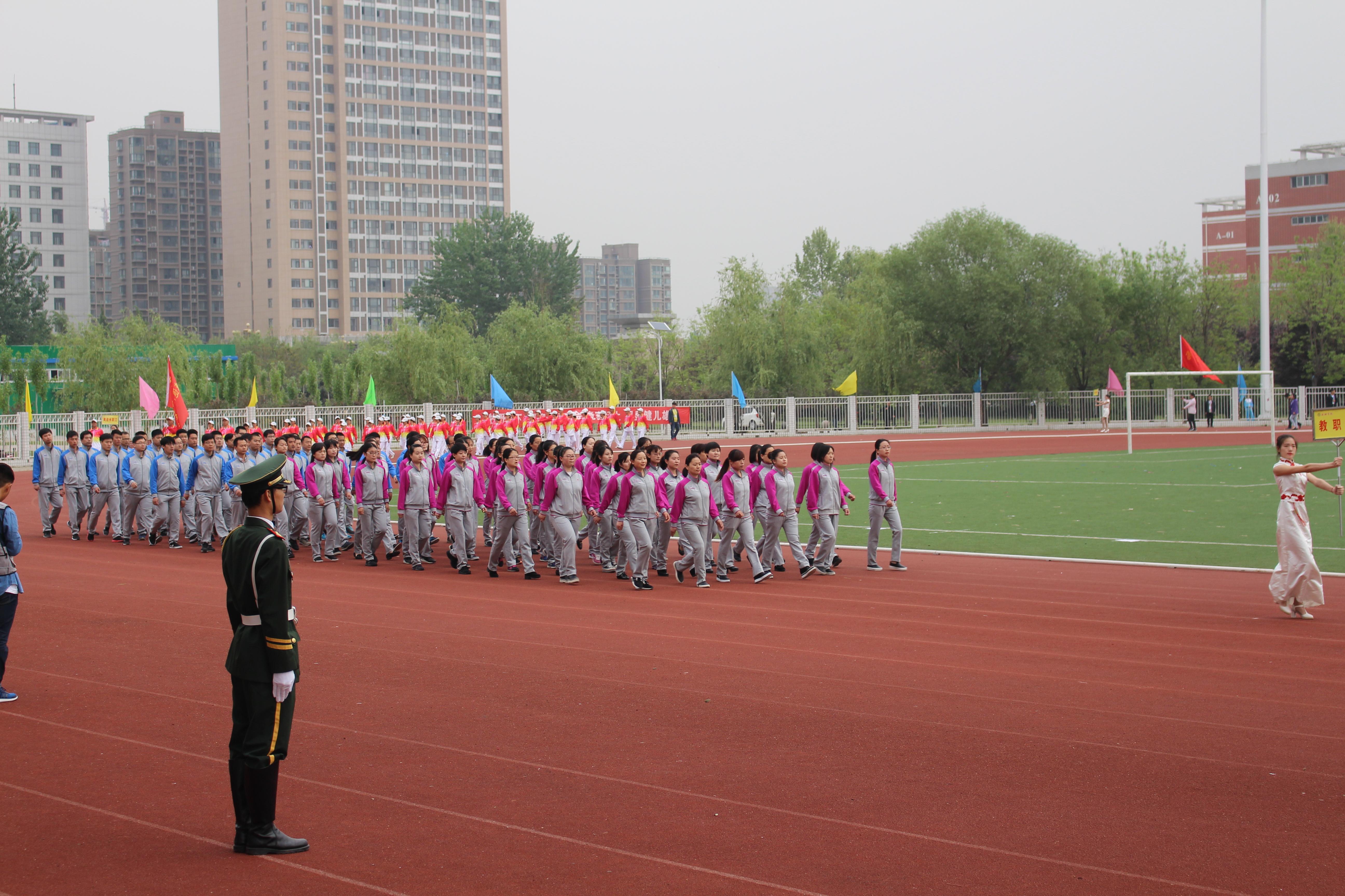 在运动会入场式上,教职工方块队队形整齐,步调一致,意志昂扬